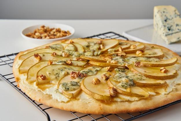 Frucht hausgemachte süße birnenpizza mit käse und honig, rustikales italienisches herzhaftes essen mit teig, seitenansicht Premium Fotos