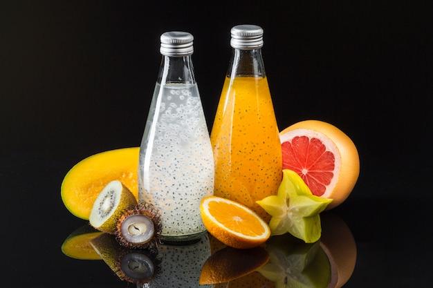 Frucht- und saftzusammensetzung auf schwarzem hintergrund Kostenlose Fotos