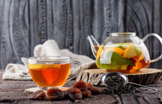 Fruchtgetränktes wasser in der teekanne mit tee, getrockneten aprikosen, holz, küchentuch, behälter-seitenansicht auf steinfliese und holzoberfläche Kostenlose Fotos