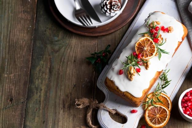 Fruchtkuchen bestäubt mit zuckerglasur, nüssen, kerngranatapfel und trockenem orange altem hölzernem. weihnachts- und winterferien hausgemachten kuchen Premium Fotos