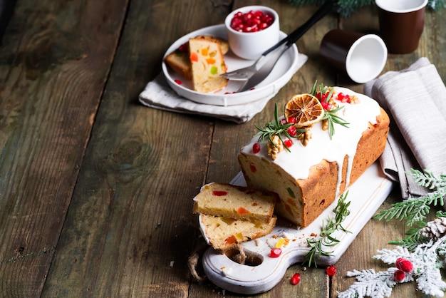 Fruchtkuchen wischte geschnitten mit zuckerglasur, nüssen, kerngranatapfel und trockenem orange altem hölzernem ab. weihnachts- und winterferien hausgemachten kuchen Premium Fotos