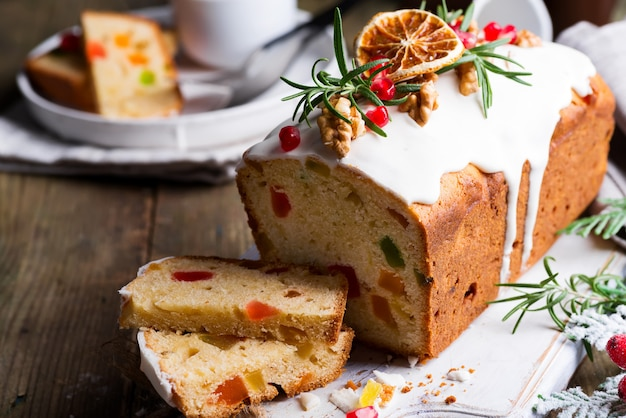 Fruchtkuchen wischte geschnitten mit zuckerglasur, nüssen, kerngranatapfel und trockener orange nahaufnahme ab. weihnachts- und winterferien hausgemachten kuchen Premium Fotos