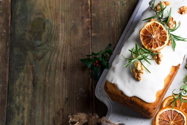 Fruchtkuchen wischte mit zuckerglasur, nüssen, kerngranatapfel und trockener orange nahaufnahme ab. weihnachts- und winterferien hausgemachten kuchen Premium Fotos