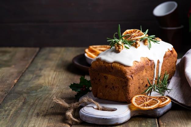 Fruchtkuchen wischte mit zuckerglasur, nüssen und trockener orange auf altem hölzernem ab. weihnachts- und winterferien hausgemachten kuchen Premium Fotos