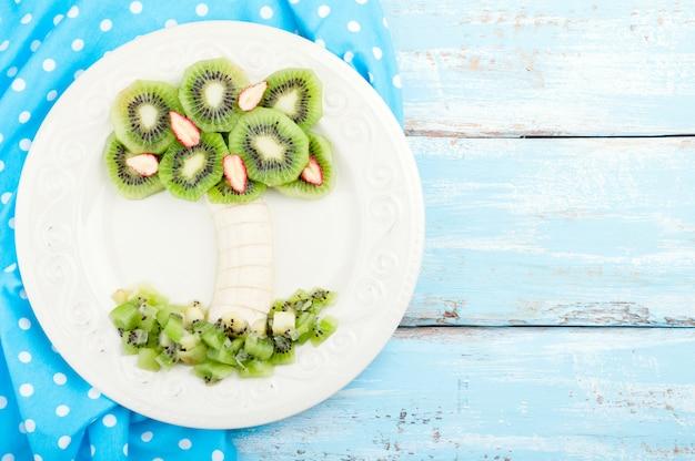 Fruchtnachtisch für kinder mit kiwi, banane und erdbeere auf hölzernem hintergrund Premium Fotos