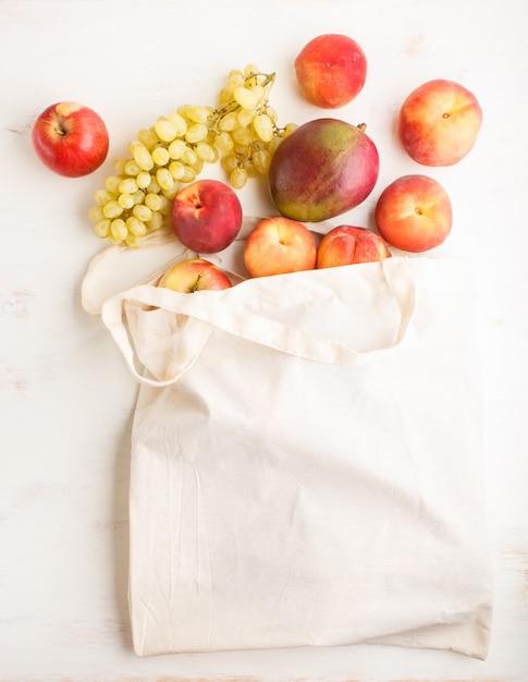 Früchte in der wiederverwendbaren baumwolltextilweißen tasche auf weißer hölzerner einkaufsspeicher- und -wiederverwertungskonzeptebenenlage des hintergrundes null Premium Fotos