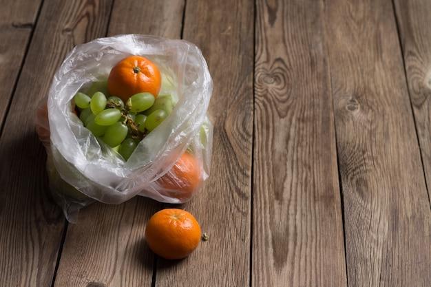 Früchte (mandarinen, äpfel, trauben) in einer plastiktüte auf einem naturholztisch. das bild zeigt die schädlichen auswirkungen von plastiktüten auf lebensmittel. Premium Fotos
