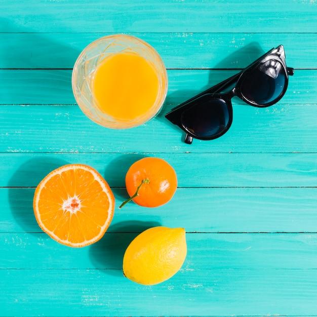 Früchte, saftglas und sonnenbrillen auf dem tisch Kostenlose Fotos