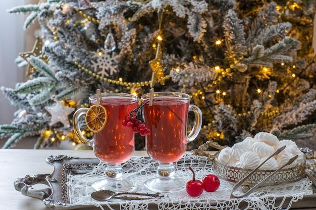 Früchtetee in bechern und baisers mit weihnachtsbaum Premium Fotos