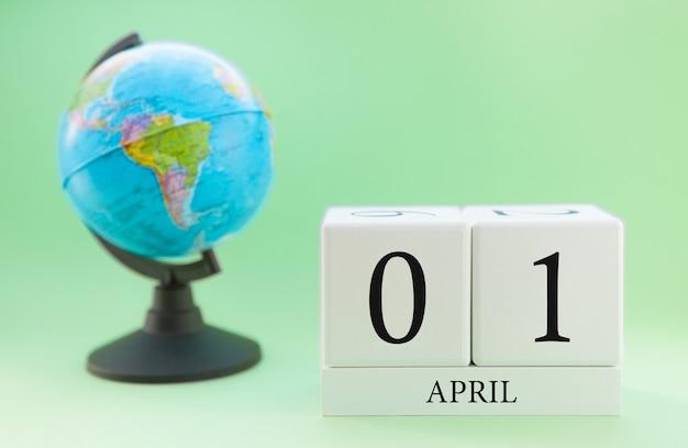 Frühling 1. april kalender. teil eines sets auf unscharfem grünem hintergrund und kugel. Premium Fotos
