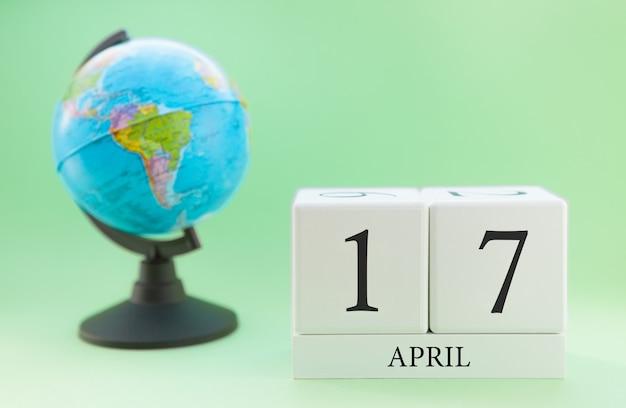 Frühling 17. april kalender. teil eines sets auf unscharfem grünem hintergrund und kugel. Premium Fotos