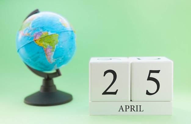 Frühling 25. april kalender. teil eines sets auf unscharfem grünem hintergrund und kugel. Premium Fotos