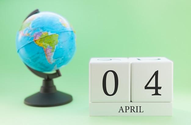 Frühling 4 april kalender. teil eines sets auf unscharfem grünem hintergrund und kugel. Premium Fotos