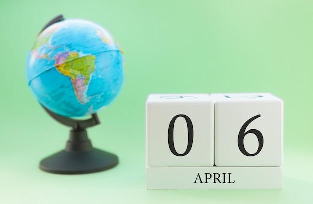 Frühling 6. april kalender. teil eines sets auf unscharfem grünem hintergrund und kugel. Premium Fotos