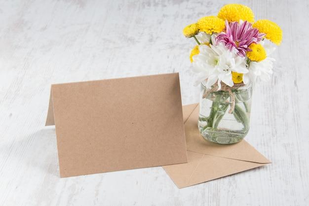 Frühling blüht blumenstrauß in einem glasvase mit kartenanmerkung und umschlag auf einem weißen hölzernen rustikalen hintergrund Premium Fotos