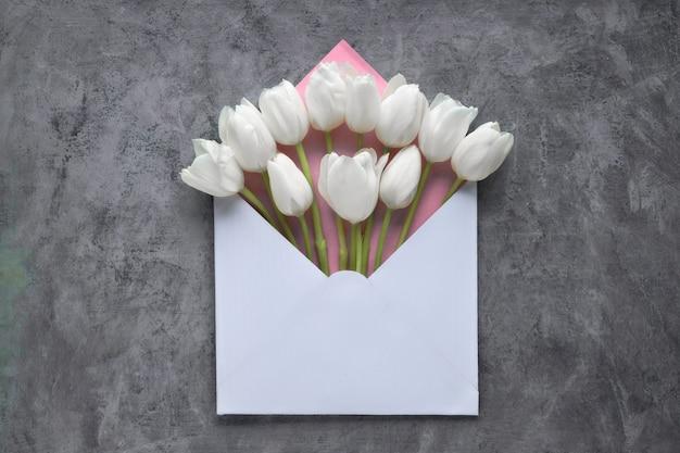 Frühling flach legen, weiße tulpen im umschlag auf dunklem strukturiertem hintergrund, Premium Fotos