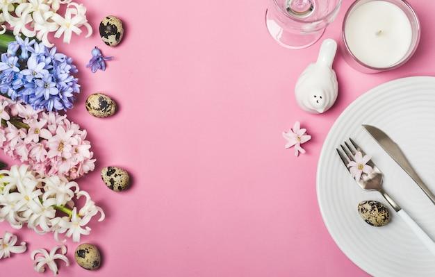Frühlings-ostertabelleneinstellung mit hyazinthenblumen auf rosa Premium Fotos
