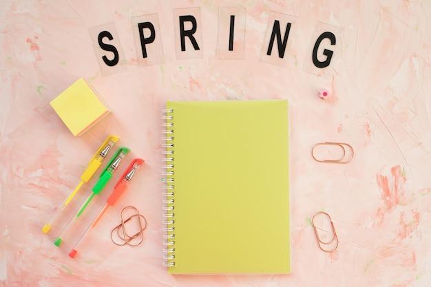 Frühlings-wort- und studentenschreibtischarbeitsplatz mit notizbuch und stiften Premium Fotos