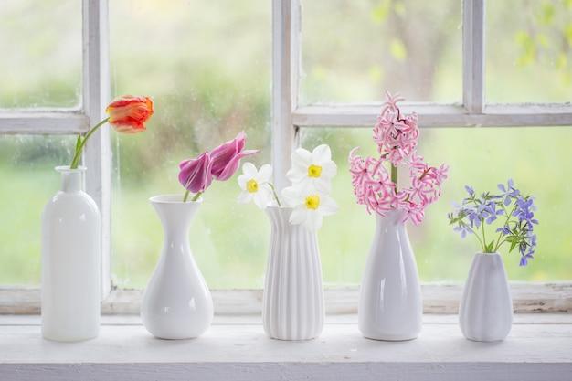 Frühlingsblumen in der weißen vase am alten fenster Premium Fotos