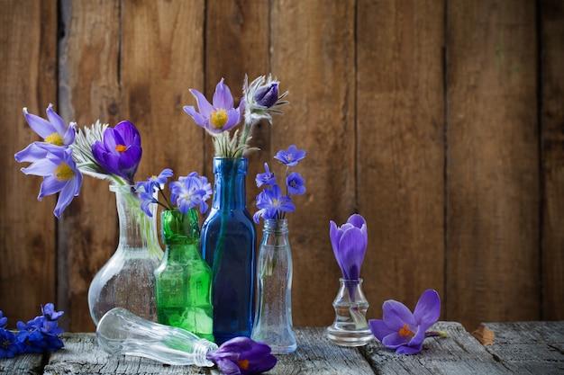 Frühlingsblumen in glasgefäßen auf einem holztisch Premium Fotos