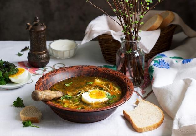 Frühlingsgrüne suppe mit kräutern, gemüse und erbsen, serviert mit ei und sauerrahm. rustikaler stil. Premium Fotos