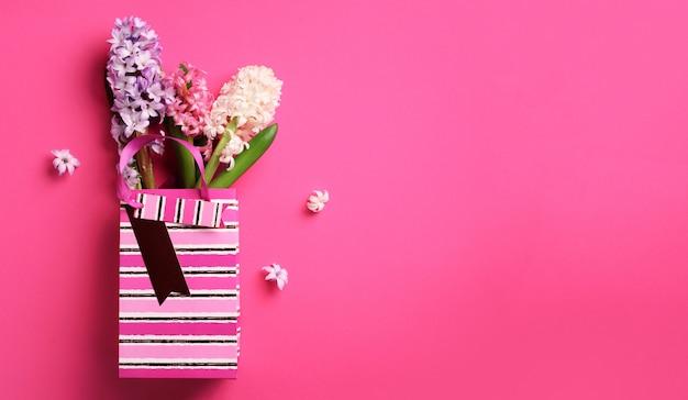 Frühlingshyazinthenblumen in der einkaufspapiertüte auf rosa schlagkräftigem pastellhintergrund. Premium Fotos