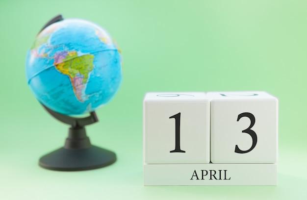 Frühlingskalender 13. april. teil eines sets auf unscharfem grünem hintergrund und kugel. Premium Fotos