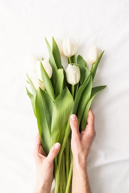 Frühlingskonzept. draufsicht der frauenhände, die weißen tulpenstrauß auf weißem stoffhintergrund halten Premium Fotos