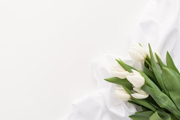 Frühlingskonzept. weißer tulpenstrauß und stoff für modellentwurf auf weißem hintergrund mit kopienraum Premium Fotos