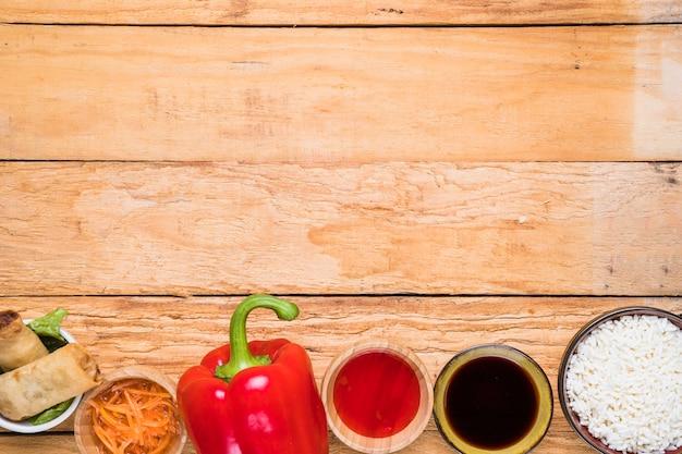Frühlingsrolle; rote paprika; soßen und reisschale auf schreibtisch aus holz Kostenlose Fotos