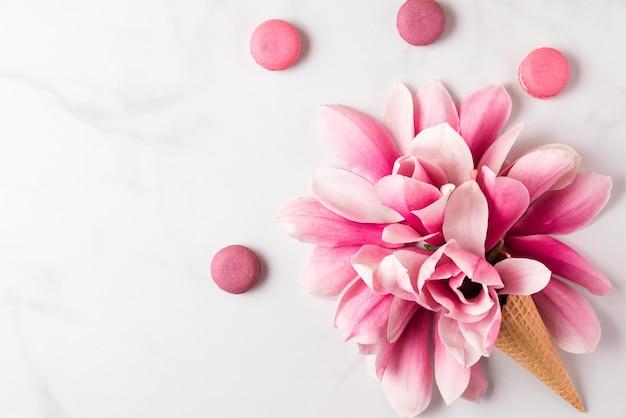 Frühlingsrosa magnolienblüten im waffelkegel mit makronen. frühlingskonzept. flach liegen. draufsicht Premium Fotos