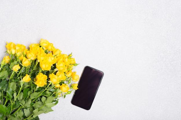 Frühlingssommerkonzept mit gelben rosenblumen und telefon auf weißem tischhintergrund Premium Fotos
