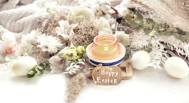 Frühlingsstillleben mit ostereiern, brennenden kerzen in einem anhänger und blumen gegen dekordetails. osterferienkonzept. Premium Fotos