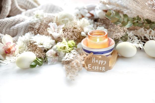 Frühlingsstillleben mit ostereiern, brennenden kerzen in einem anhänger und blumen vor dem hintergrund der dekordetails. osterferienkonzept. Premium Fotos