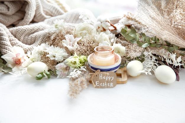 Frühlingsstillleben mit ostereiern, kerzen in einem anhänger und blumen gegen dekor details. osterferienkonzept. Premium Fotos