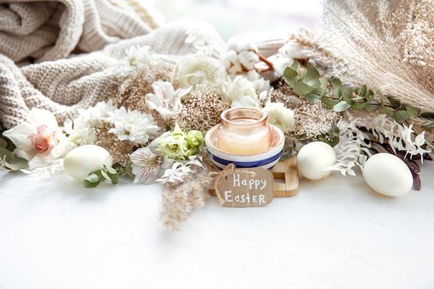 Frühlingsstillleben mit ostereiern, kerzen in einem anhänger und blumen vor dem hintergrund der dekordetails. osterferienkonzept. Premium Fotos