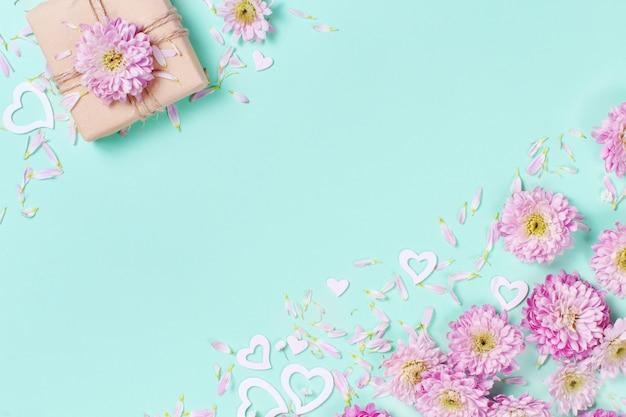 Frühlingszusammensetzung mit blumen, blütenblättern, herzen und geschenkbox auf einem pastellhintergrund Premium Fotos