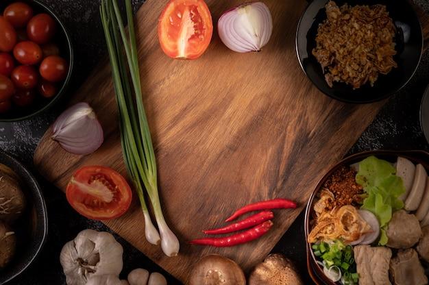 Frühlingszwiebeln, paprika, knoblauch und shiitake-pilze auf einem holzteller Kostenlose Fotos