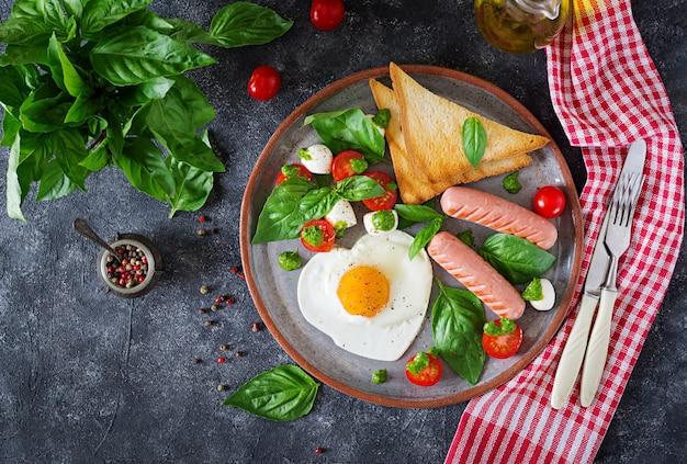 Frühstück am valentinstag - spiegeleier in form, herz, wurst, toast und caprese-salat Premium Fotos