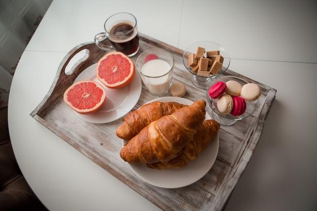 Frühstück auf einem tablett - kaffee, croissant, frischer saft Premium Fotos