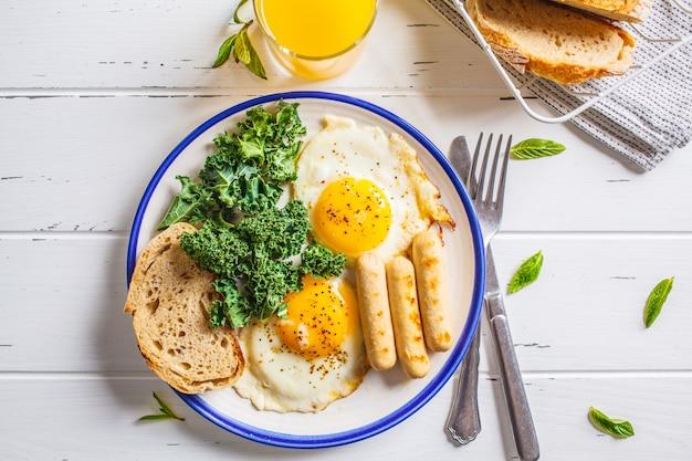 Frühstück diente mit spiegeleiern, salat, muffins und orangensaft auf weißem holztisch. Premium Fotos