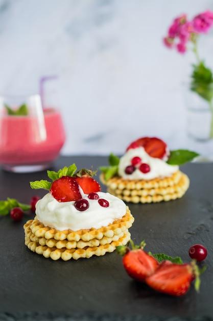 Frühstück mit bio-smoothie und köstlichen belgischen waffeln mit schlagsahne und erdbeeren Premium Fotos