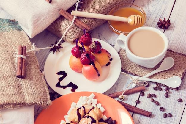Frühstück mit croissants, honig und häppchen von erdbeeren und aprikosen Premium Fotos
