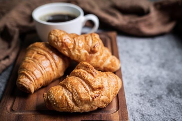 Frühstück mit frischen croissants und einer tasse schwarzen kaffees auf holzbrett Premium Fotos