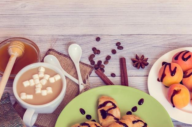 Frühstück mit kaffee, croissants, aprikosen, honig, zimt und anis Premium Fotos