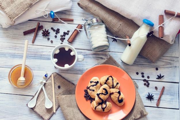 Frühstück mit kaffee, croissants, milch, honig, zucker, zimt, anis Premium Fotos