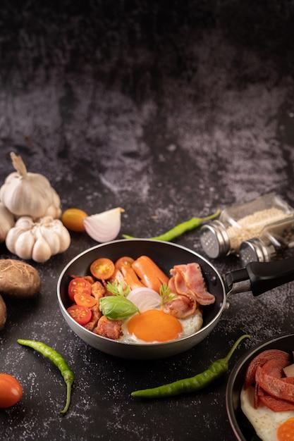 Frühstück mit spiegeleiern, wurst und schinken in einer pfanne mit tomaten. chili und basilikum Kostenlose Fotos