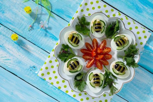 Frühstück oder mittagessen für kinder - hart gekochte eierbiene. frohe ostern essen für die kinder. draufsicht mit kopierraum. Premium Fotos