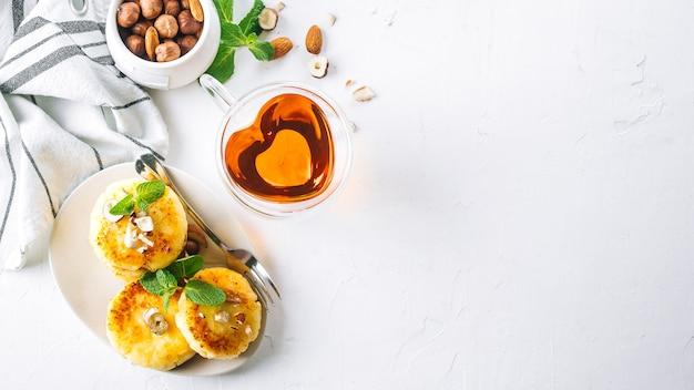 Frühstück oder mittagessen konzept. hüttenkäsepfannkuchen mit honig, nüssen und minze. bannerbild Premium Fotos