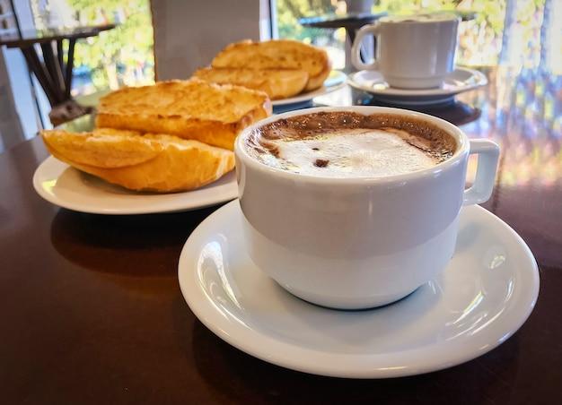 Frühstücken sie in brasilien mit dem französischen brot, das mit butter auf der platte mit capuccino auf tabelle geröstet wird. Premium Fotos